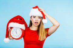 Woman wearing Santa Claus costume holding clock Stock Photos