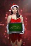 Woman wearing santa claus costume holding laptop with merry christmas writing Stock Images