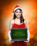 Woman wearing santa claus costume holding laptop with merry christmas writing Royalty Free Stock Image
