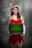 Woman wearing santa claus costume holding laptop with merry christmas writing Stock Photography