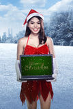 Woman wearing santa claus costume holding laptop with merry christmas writing Stock Photo