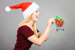 Woman wearing Santa Claus costume holding trolley Royalty Free Stock Photos