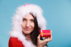 Woman wearing santa claus costume holds gift box on blue Royalty Free Stock Images