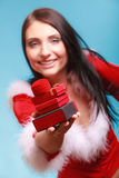 Woman wearing santa claus costume holds gift boxes on blue Royalty Free Stock Photos