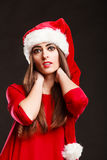Woman wearing santa claus hat on black Stock Photography