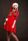 Woman wearing santa claus hat on black. Christmas time. Young woman wearing santa claus hat red dress on black background. Studio shot Royalty Free Stock Image
