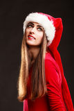 Woman wearing santa claus hat on black. Christmas time. Young woman wearing santa claus hat red dress on black background. Studio shot Royalty Free Stock Photos