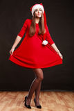 Woman wearing santa claus hat on black. Christmas time. Young woman wearing santa claus hat red dress on black background. Studio shot Stock Images
