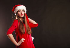 Woman wearing santa claus hat on black. Christmas time. Young woman wearing santa claus hat red dress on black background. Studio shot Stock Photos