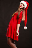 Woman wearing santa claus hat on black. Christmas time. Young woman wearing santa claus hat red dress on black background. Studio shot Stock Image