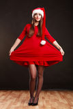 Woman wearing santa claus hat on black. Christmas time. Young woman wearing santa claus hat red dress on black background. Studio shot Royalty Free Stock Photo