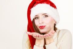 Woman wearing santa claus hat blowing kiss. Christmas time. Young latin woman wearing santa claus hat sending kiss. Studio shot Stock Photos