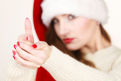 Woman wearing santa claus hat portrait. Christmas time. Young latin woman wearing santa claus hat pointing at you with finger. Studio shot Royalty Free Stock Photo
