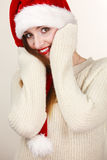 Woman wearing santa claus hat portrait. Christmas time. Young latin woman wearing santa claus hat white warm sweater warming her hands. Studio shot Royalty Free Stock Photo