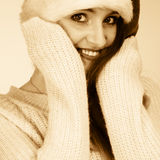 Woman wearing santa claus hat portrait. Christmas time. Young latin woman wearing santa claus hat white warm sweater warming her hands. Studio shot sepia tone Royalty Free Stock Photo