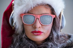 Woman wearing Santa Claus hat and sunglasses listening to music Stock Images