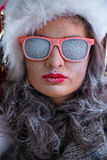 Woman wearing Santa Claus hat and sunglasses listening to music Royalty Free Stock Photo