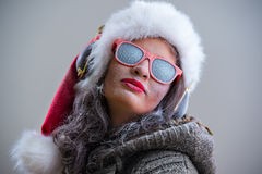 Woman wearing Santa Claus hat and sunglasses listening to music Royalty Free Stock Photography
