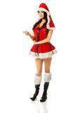 Woman wearing santa clothes pointing left Royalty Free Stock Image