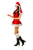 Woman wearing santa clothes pointing Royalty Free Stock Image