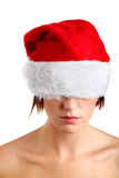 Woman wearing santa hat. Young woman wearing a santa hat with her eyes covered Royalty Free Stock Image
