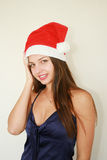 Woman wearing santa hat Stock Images