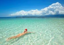 Woman is wearing Santa hat in bikini and swim in water at beach. Stock Image