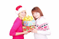 Woman wearing santa hat giving christmas present t Stock Photos