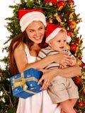 Woman wearing Santa hat holding baby under Christmas tree. Stock Photos