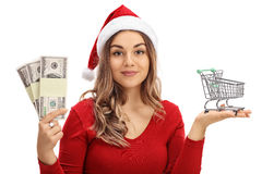 Woman wearing Santa hat holding small shopping cart and money bu. Young woman wearing a Santa hat holding a small empty shopping cart and money bundles isolated Royalty Free Stock Images