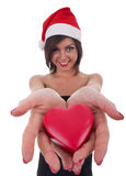 Woman wearing santa hat holds a heart. Beautiful young woman wearing santa hat holding an heart Royalty Free Stock Photos