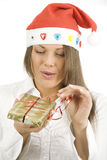 Woman wearing Santa hat opening a gift Royalty Free Stock Photography