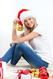 Woman wearing santa hat sitting on the floor Stock Photos