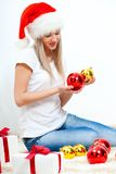 Woman wearing santa hat sitting on the floor Royalty Free Stock Photos