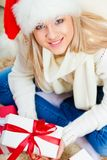 Woman wearing santa hat sitting on the floor Royalty Free Stock Photo