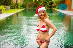 Woman wearing Santa hat while on winter holidays. In the tropical pool Royalty Free Stock Photo