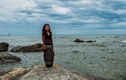 Woman standing on Rock in Sarong stock images