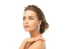 Woman wearing shiny diamond earrings Royalty Free Stock Images