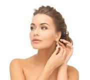 Woman wearing shiny diamond earrings. Close-up of beautiful woman wearing shiny diamond earrings Stock Image