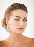 Woman wearing shiny diamond earrings Royalty Free Stock Photos