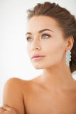 Woman wearing shiny diamond earrings. Close up of beautiful woman wearing shiny diamond earrings Stock Photos