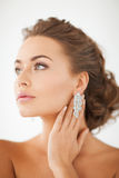 Woman wearing shiny diamond earrings Stock Photo
