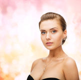Woman wearing shiny diamond earrings and pendant Stock Photography