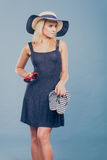 Woman wearing short dress holding flip flops and sunglasses Royalty Free Stock Photo