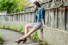 Woman wearing short floral print dress and denim jacket sitting. A young woman sitting along a wooden fence in a urban  or suburban setting wearing a short Royalty Free Stock Photos