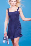 Woman wearing short navy dress holding flip flops Stock Photo