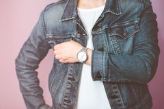 Woman wearing silver wristwatch and jeans jacket. Standing in front of pastel pink wall royalty free stock image