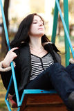 Woman wearing sitting on a swing in a park. Young woman wearing sitting on a swing in a park Stock Image