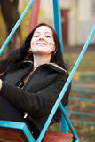 Woman wearing sitting on a swing in a park. Young woman wearing sitting on a swing in a park Stock Photos