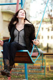Woman wearing sitting on a swing in a park. Young woman wearing sitting on a swing in a park Stock Photography